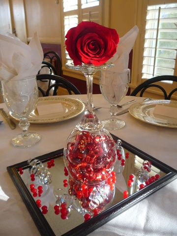 centros de mesa con rosas rojas y copas
