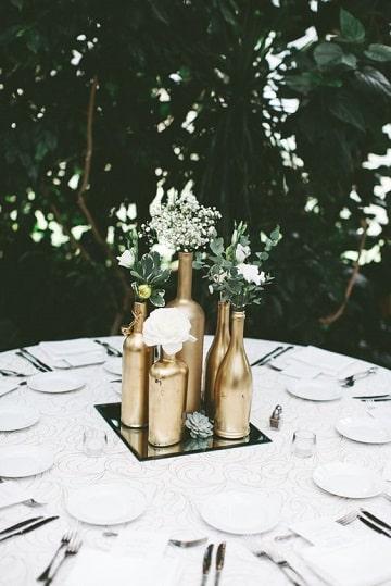 centros de mesa dorados con botellas