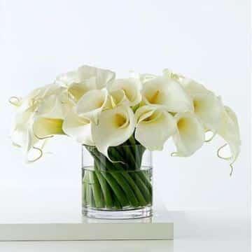 arreglos florales en cilindros de vidrio con lirios