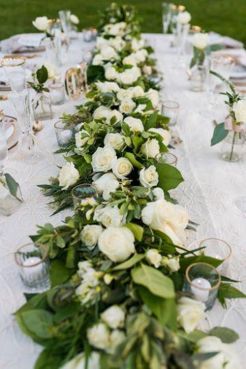 centros de mesa de rosas blancas en mesas largas